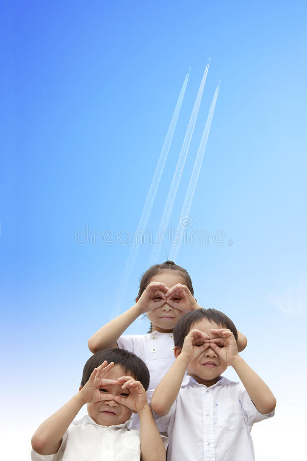 Happy kids watching the aircraft flying. Three happy asian kids watching the aircraft flying through to sky royalty free stock photos