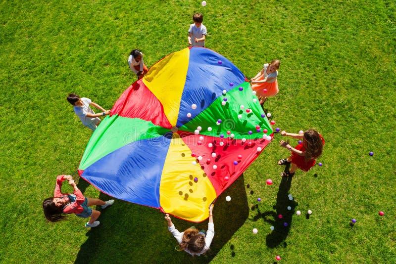Happy kids waving rainbow parachute full of balls stock image