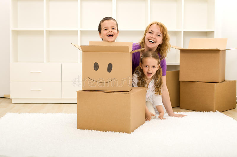 Happy kids and woman having fun in their new home. Playing among cardboard boxes stock images
