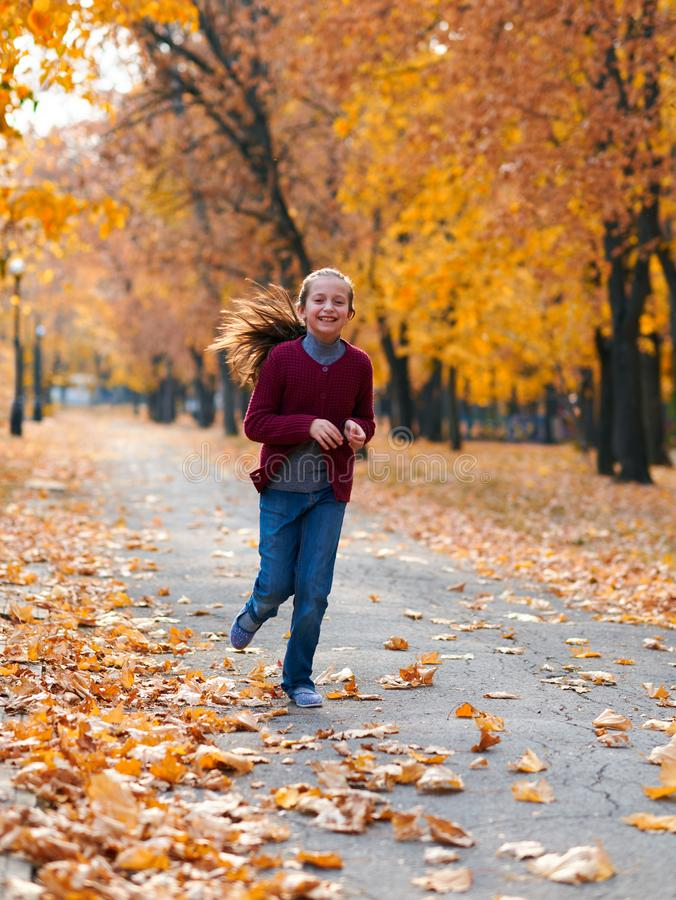 Happy-Kind Mädchen, das im Herbststädpark läuft, spielt, posiert, lächelt und Spaß hat. Hellgelbe Bäume und Blätter lizenzfreie stockbilder