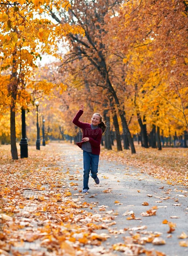 Happy-Kind Mädchen, das im Herbststädpark läuft, spielt, posiert, lächelt und Spaß hat. Hellgelbe Bäume und Blätter stockbild