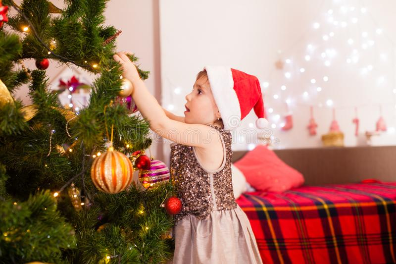 Happy Kind Mädchen schmückt Weihnachtsbaum zu Hause stockbilder