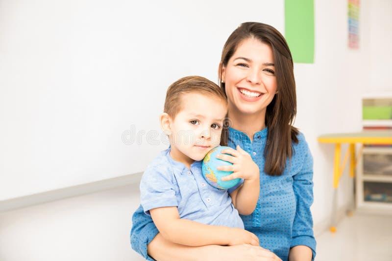 Happy kindergarten teacher at work stock image