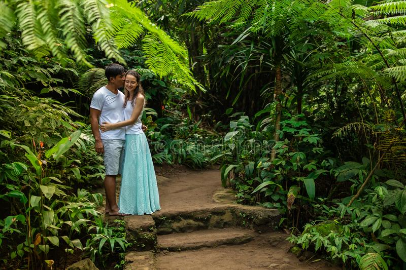 Happy kissing multiracial couple hugging on walking trail in tropical forest. Young mixed race couple on vacation in Asia. Ubud, stock image