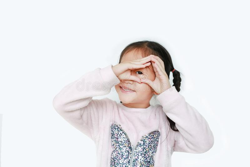 Happy kleines Mädchen, das Dreieck macht und durch ihre Hände isoliert über weißen Hintergrund sieht lizenzfreie stockfotografie