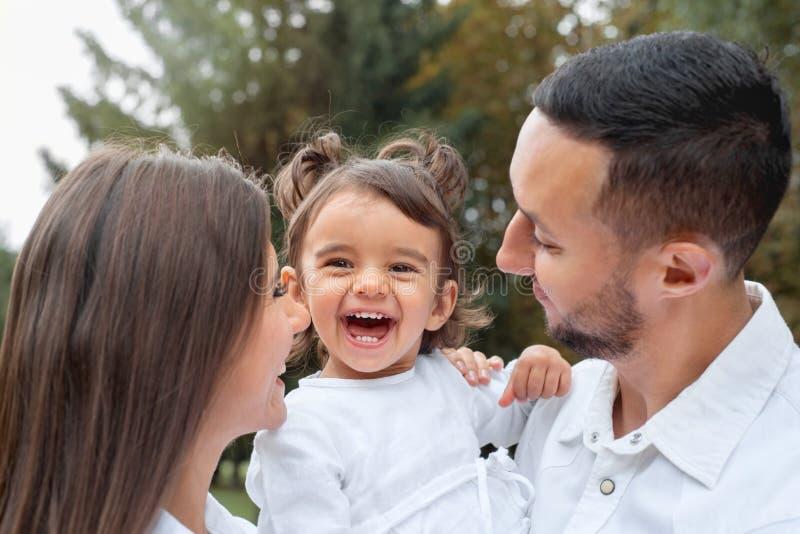 Happy kleines Mädchen lachte mit ihren Eltern im Park stockfotos