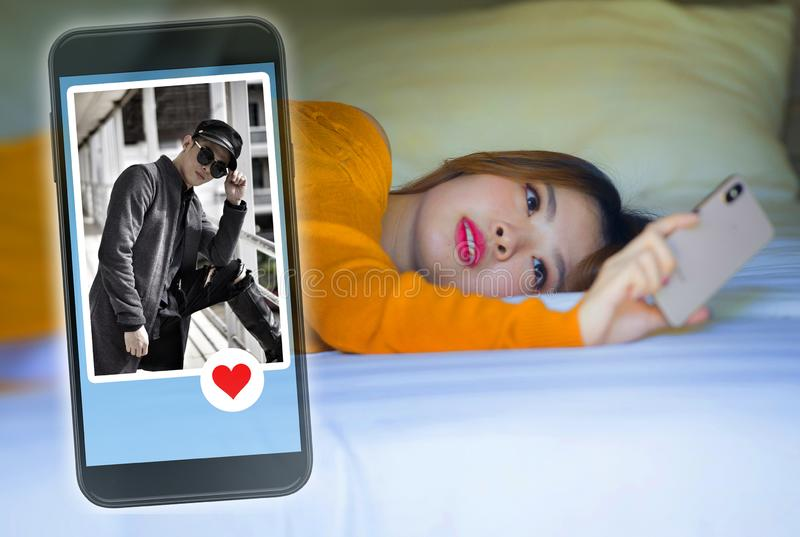 Happy Korean woman in bed using mobile phone doing video call or flirting online via social media dating app with cool man in royalty free stock image