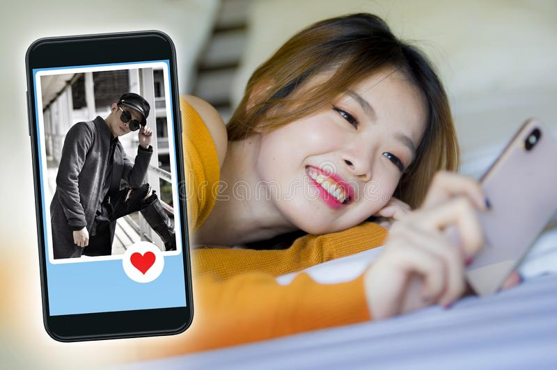 Happy Korean woman in bed using mobile phone doing video call or flirting online via social media dating app with cool man in stock images
