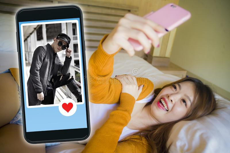 Happy Korean woman in bed using mobile phone doing video call or flirting online via social media dating app with cool man in stock photography