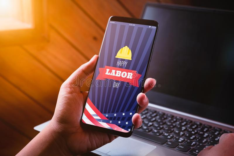 Happy labdor day mockup mobile phone concept. Close up business woman hand holding smart phone with Happy Labor Day on screen with stock images