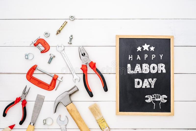 Happy Labor Day background concept. Flat lay of construction handy tools with black chalkboard with happy labor day text over stock image