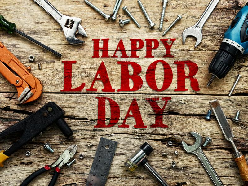 Happy Labor day text in red color on wooden background with construction repair tools. stock photography