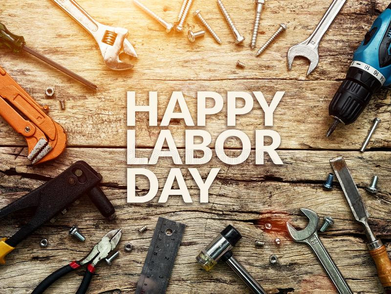 Happy Labor day text in white color on wooden background with construction repair tools. royalty free stock photo
