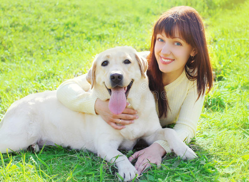 Happy labrador retriever dog and owner woman lying on the grass. In sunny summer day stock photo