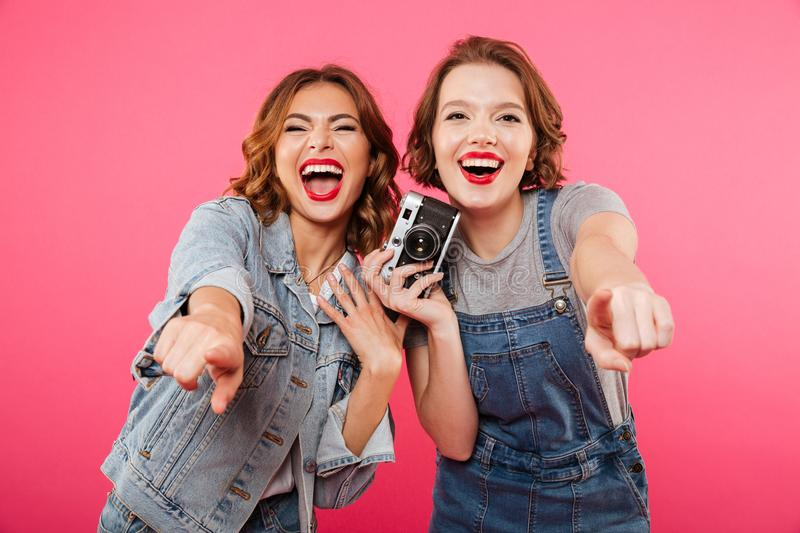 Happy ladies make photo by camera and pointing to you. stock photo