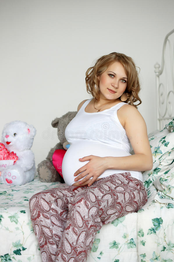 Happy lady. Beautiful pregnant blonde woman posing in studio royalty free stock photos