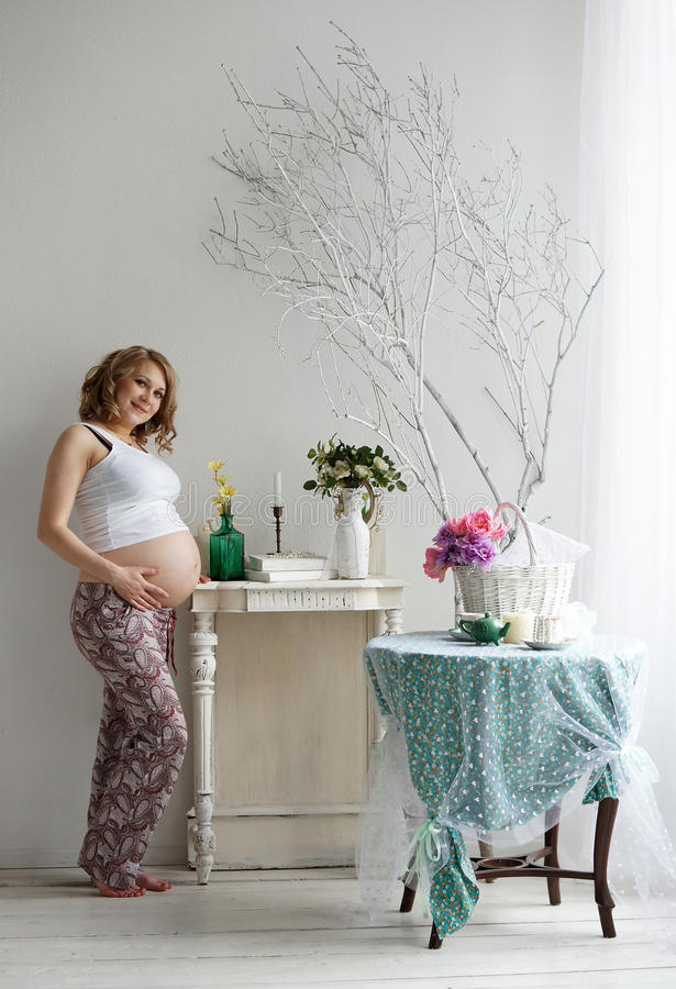 Happy lady. Beautiful pregnant blonde woman posing in studio royalty free stock photography