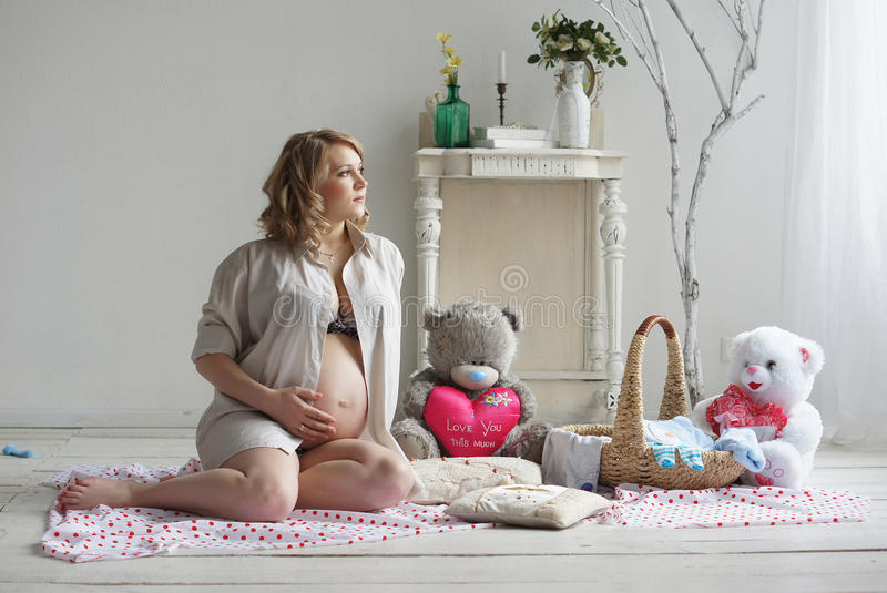 Happy lady. Beautiful pregnant blonde woman posing in studio stock photos