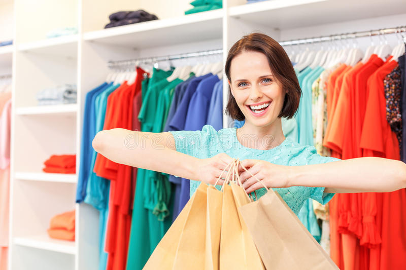 Happy lady boasting of purchase in shop stock images