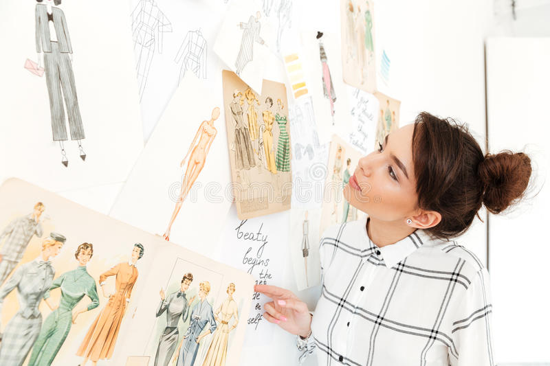 Happy lady fashion illustrator standing near a lot of illustrations. Image of young happy lady fashion illustrator standing near a lot of illustrations and stock photos