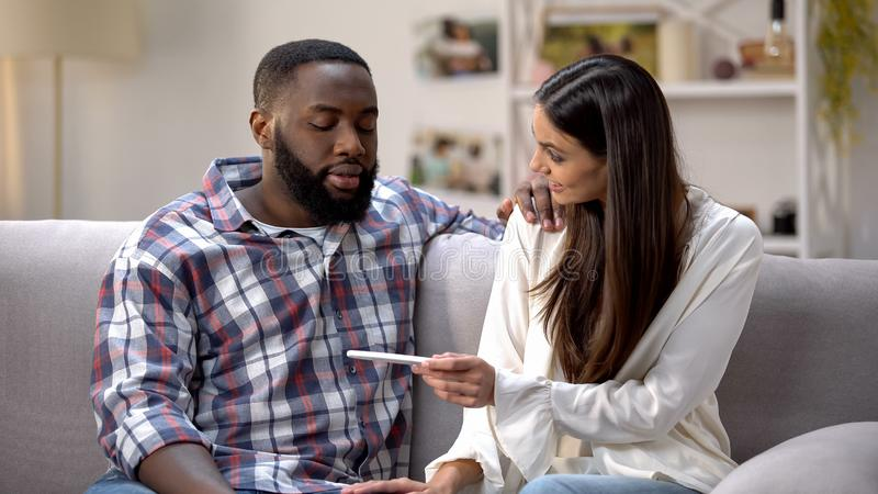 Happy lady showing pregnancy test to Afro-American boyfriend, positive result royalty free stock images
