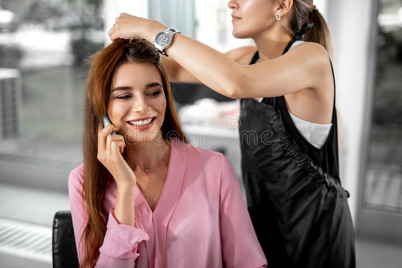 Beautiful smiling woman talking on phone in beauty salon. Happy lady sitting on armchair and talking on the smartphone while hairdresser doing styling stock images