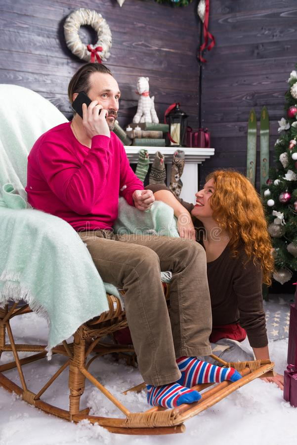 Happy lady smiling while her husband talking on the phone. Cheerful relaxed young women sitting near the rocking chair and smiling to her husband talking on the royalty free stock images
