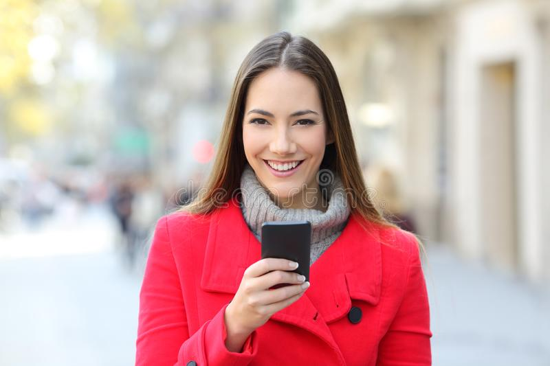 Happy lady in the street looks at you holding phone. Front view portrait of a happy lady in red in the street looks at you holding a smart phone stock photography
