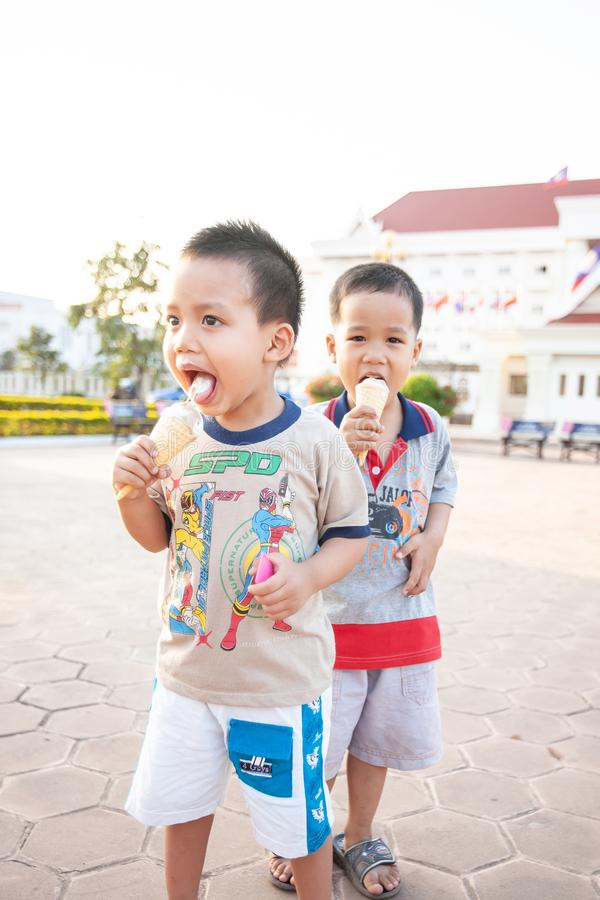 Happy Laotians twin boys enjoy eating melting ice cream cones on a hot summer day royalty free stock images