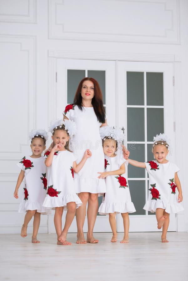Happy large family of mother with four daughters in embroidered white dresses opposite the door in the interior stock image