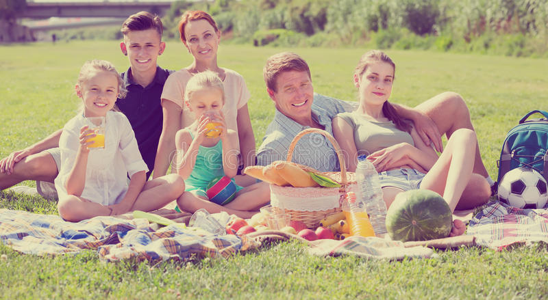 Happy large family of six having picnic on green lawn in park. Happy large family of six having picnic outdoors on green lawn in park royalty free stock images