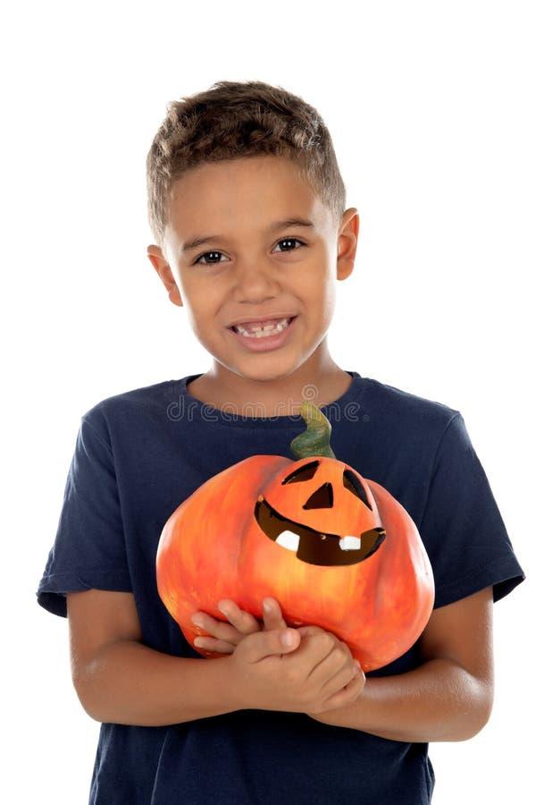 Happy latin boy holding a big pumpkin royalty free stock images
