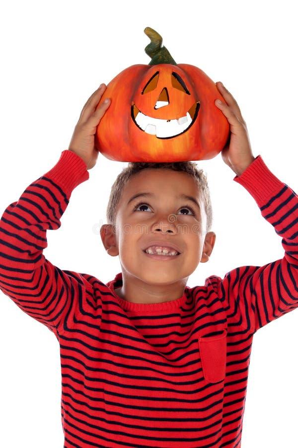 Happy latin boy holding a big pumpkin royalty free stock photo