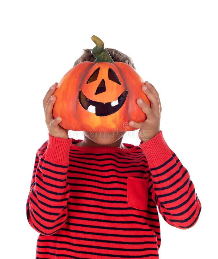 Happy latin boy holding a big pumpkin royalty free stock photography