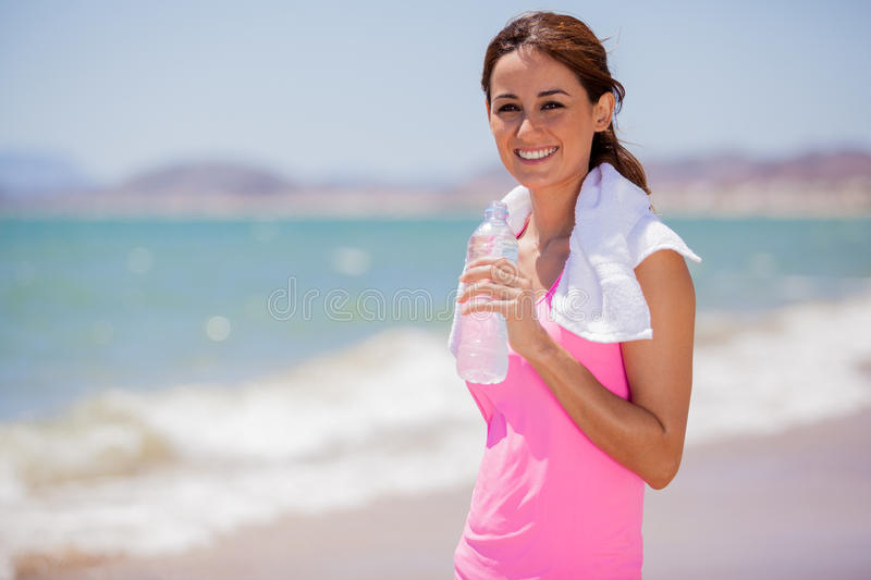 Happy Latin girl drinking water. Beautiful young brunette drinking water and cooling off after running at the beach royalty free stock photography