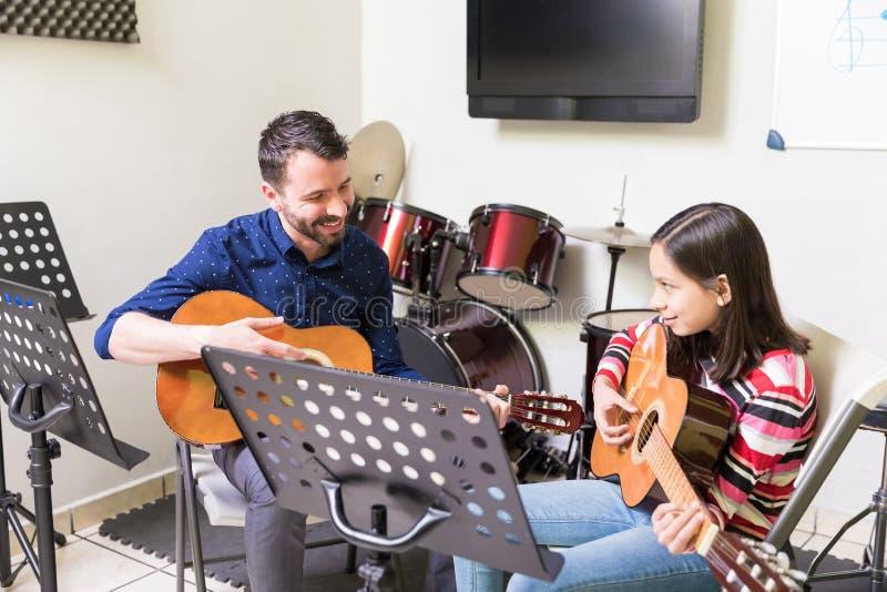 Schoolgirl Learning Guitar From Friendly Teacher stock photography
