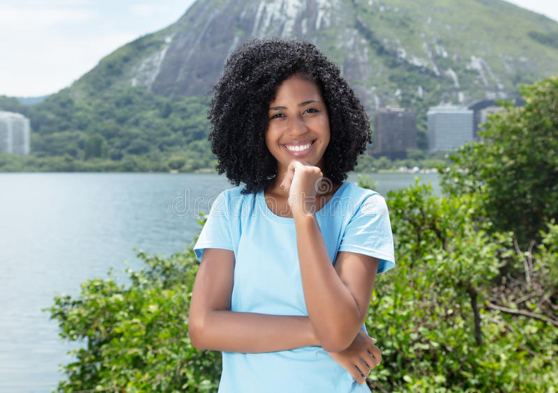 Happy latin woman with curly black hair outdoor on a sea royalty free stock photography
