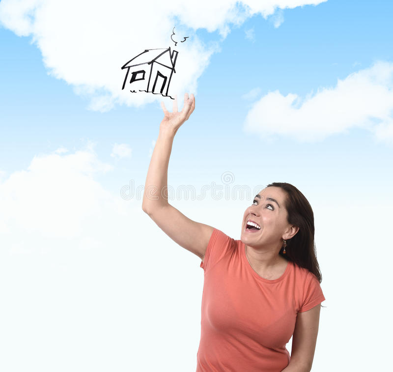 Happy Latin woman touching dream of new house real estate concept. Young happy Hispanic woman thinking and touching clouds dreaming of new house looking up on stock photos