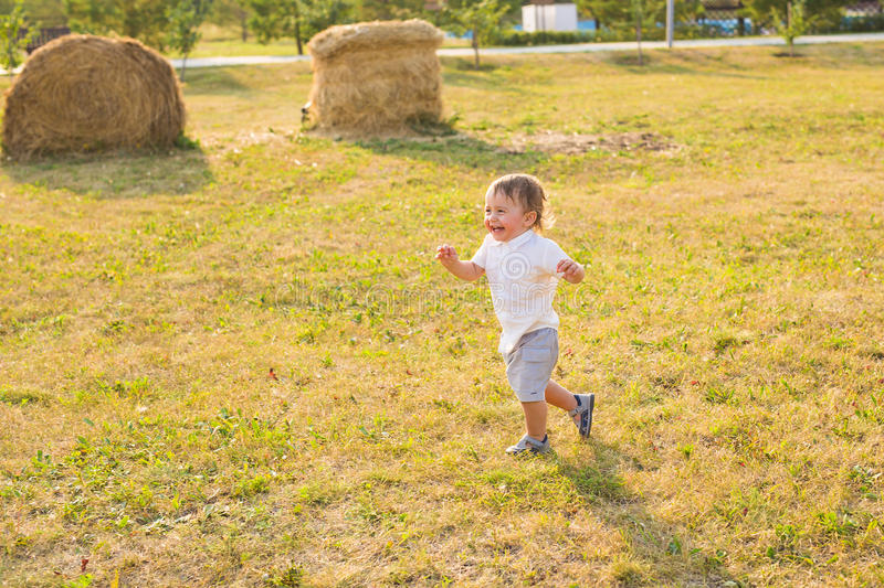 Happy laughing baby boy playing on summer or autumn field. Happy laughing baby boy running on summer or autumn field stock photos
