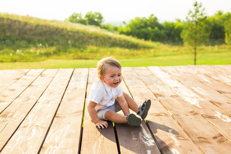Happy laughing baby boy playing on summer or autumn nature. Happy laughing baby boy running on summer or autumn field royalty free stock photos