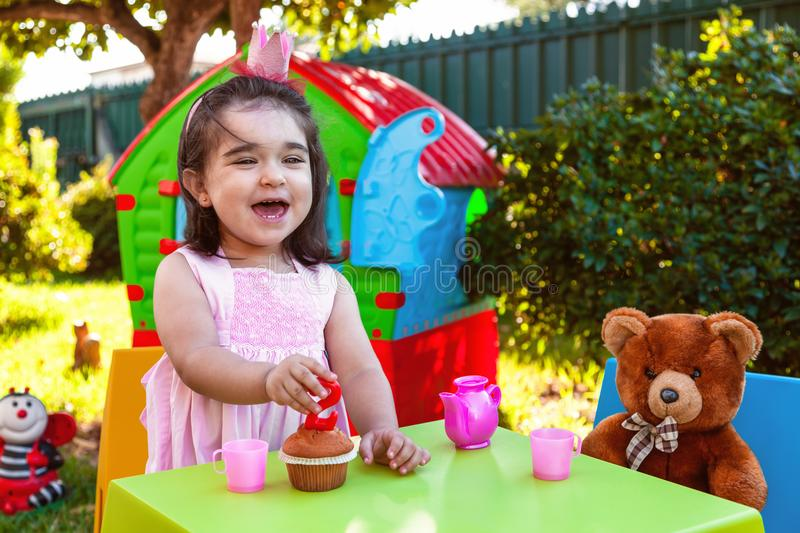Happy laughing baby toddler girl in outdoor second birthday party holding candle. Best friend Teddy Bear, playhouse and tea set. Pink dress and crown stock photography