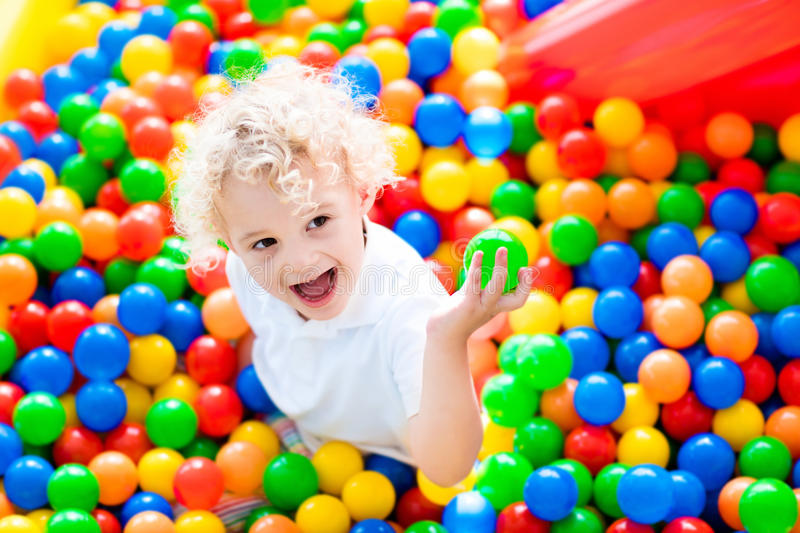 Child playing in ball pit on indoor playground royalty free stock photo