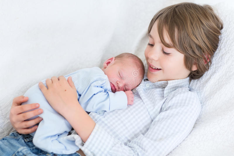 Happy laughing boy holding his sleeping newborn baby brother stock photos