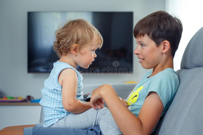 Happy laughing boy talking to his baby sister indoors. Happy laughing boy talking to his baby sister at home stock photography