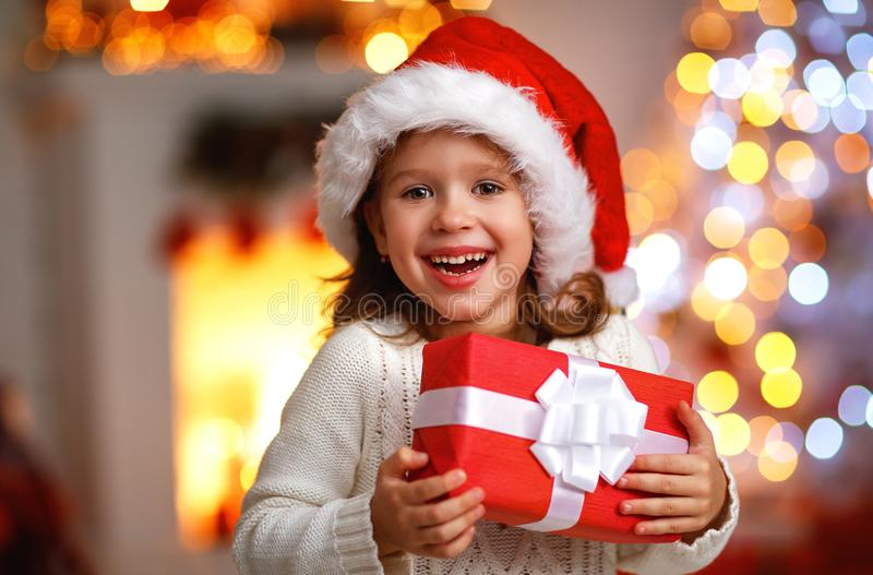 Happy laughing child girl with christmas present. At home stock image