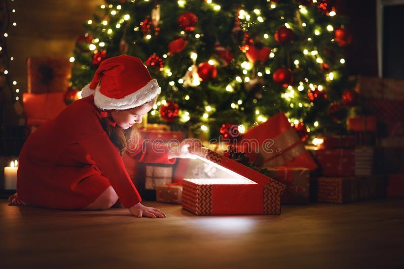 Happy laughing child girl with magic gift on Christmas Eve stock photos
