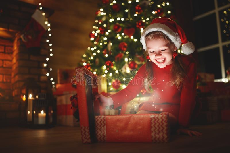 Happy laughing child girl with magic gift on Christmas Eve royalty free stock photo