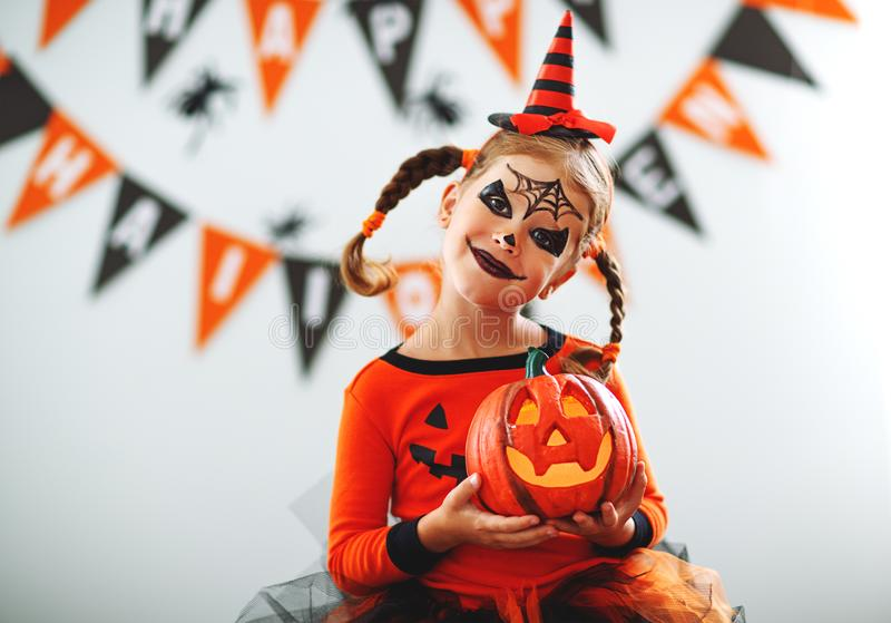 Happy child girl in pumpkin costume to halloween. Happy laughing child girl in pumpkin costume to halloween stock image