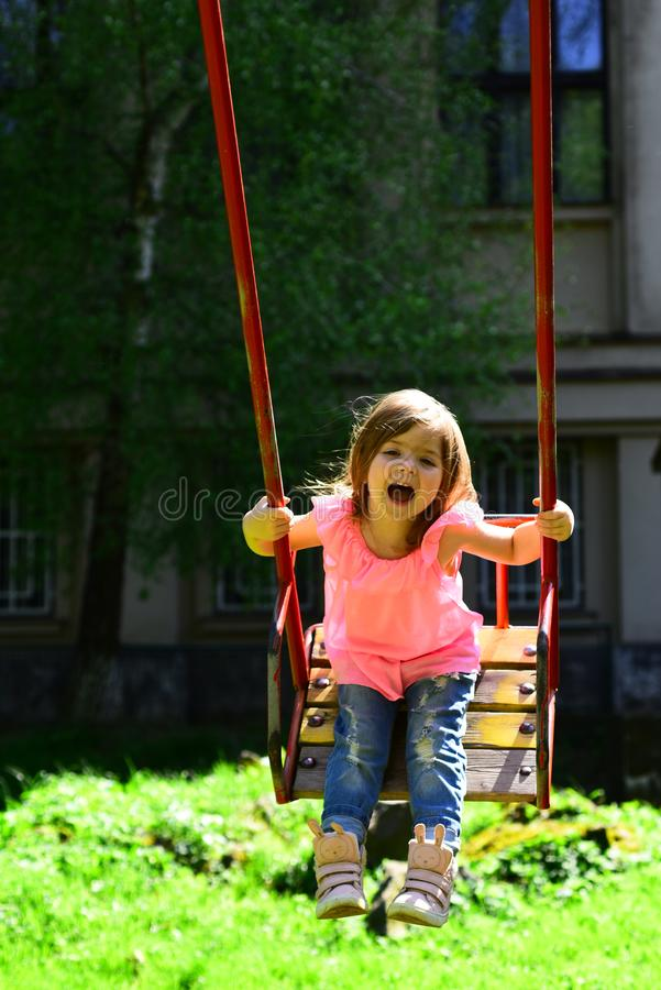 Happy laughing child girl on swing. childhood daydream .teen freedom. Playground in park. Small kid playing in summer royalty free stock images