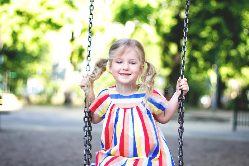 Happy laughing child girl on swing. stock photo
